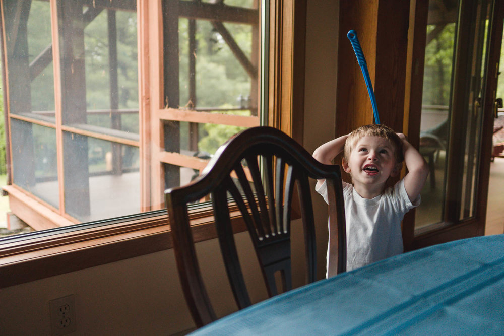 A little boy plays with a fly swatter.