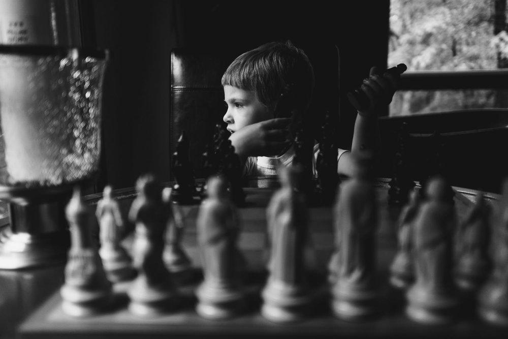 A little boy plays chess.