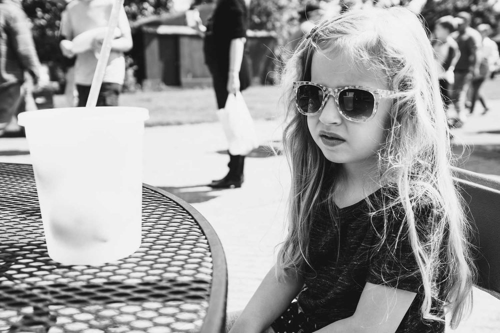A little girl in sunglasses sits at a table with a large lemonade.
