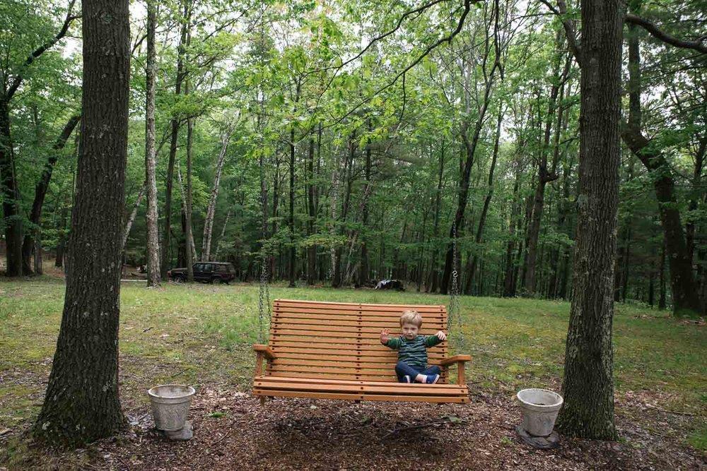 A little boy swings on a swing in the woods.