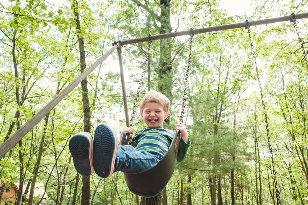A little boy laughs as he swings on a swing surrounded by trees.