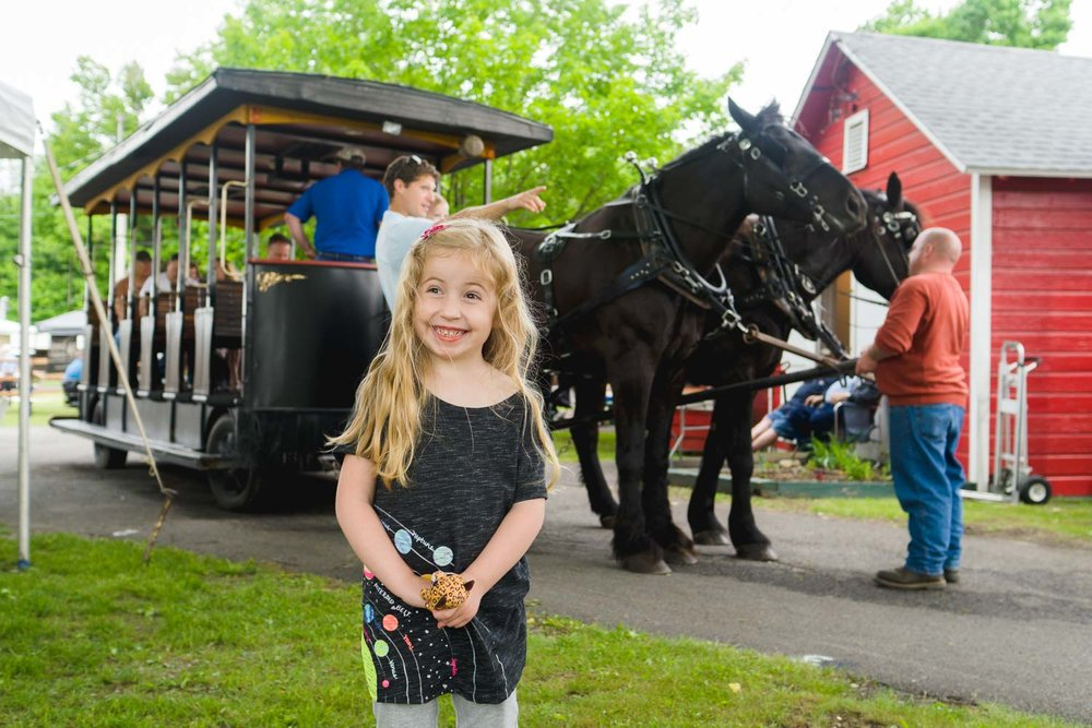A little girl smiles in front of a horse carriage.