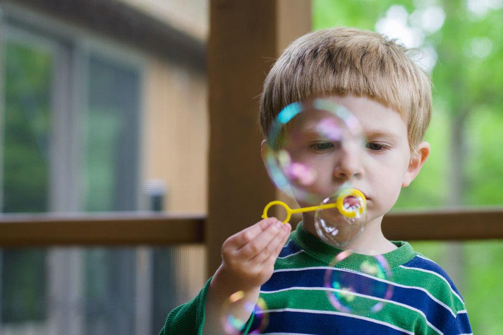A little boy blows bubbles.