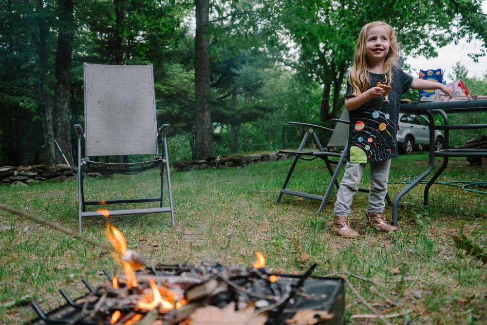 A little girl preps s'mores by the bonfire.