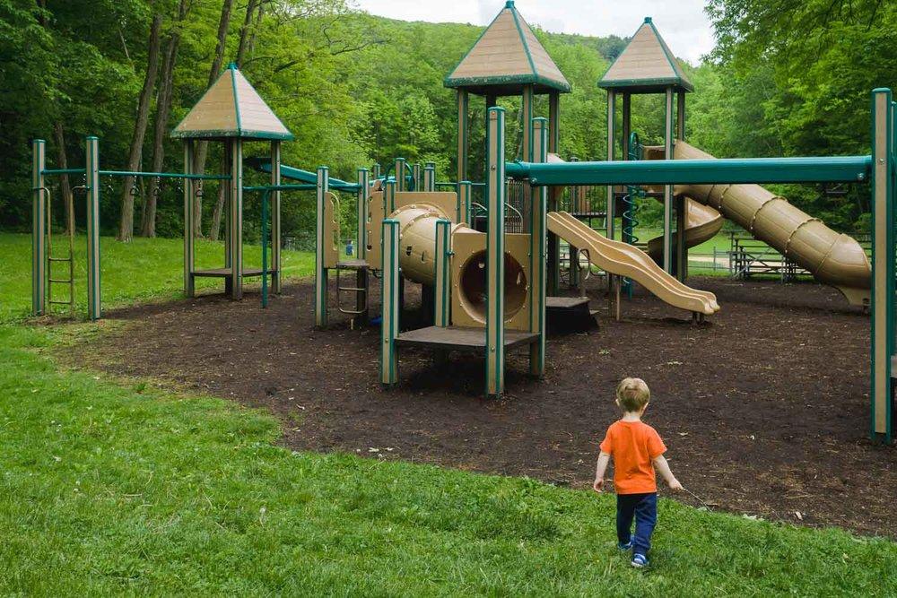 A little boy walks toward a playground.
