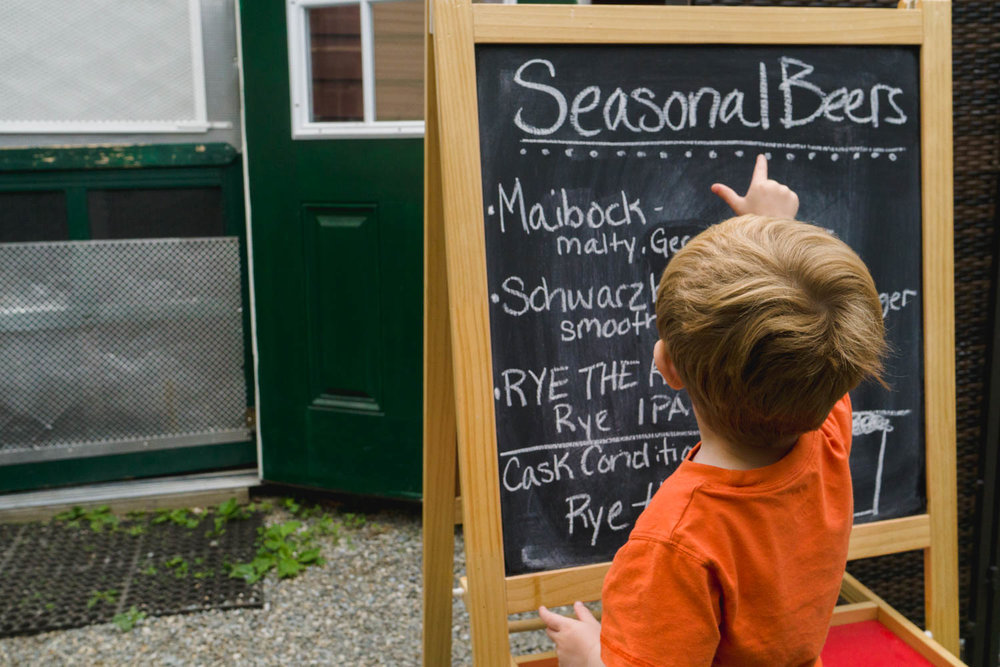 A little boy reads a chalkboard with beer specials.