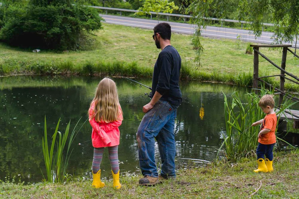 A father and his kids fish in a pond.