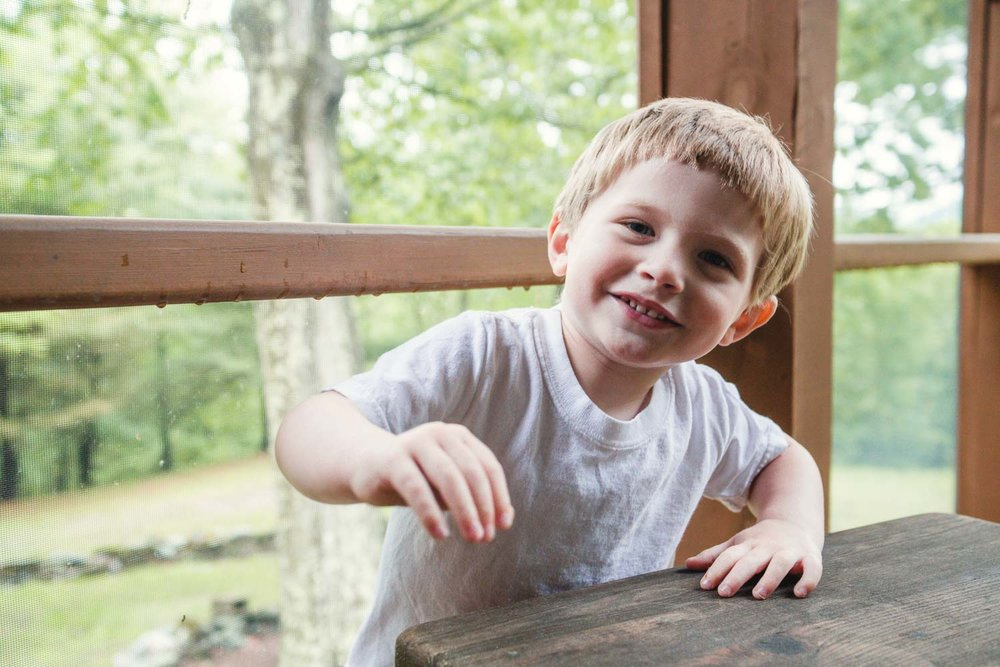 Portrait of a little boy on the porch of a house in the woods.