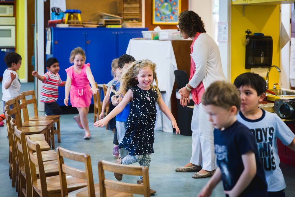 A happy little girl runs through a classroom with her classmates.