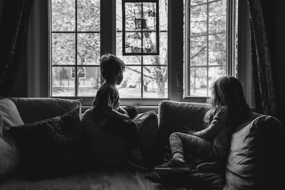 A boy and girl sit on the couch and look out the window.