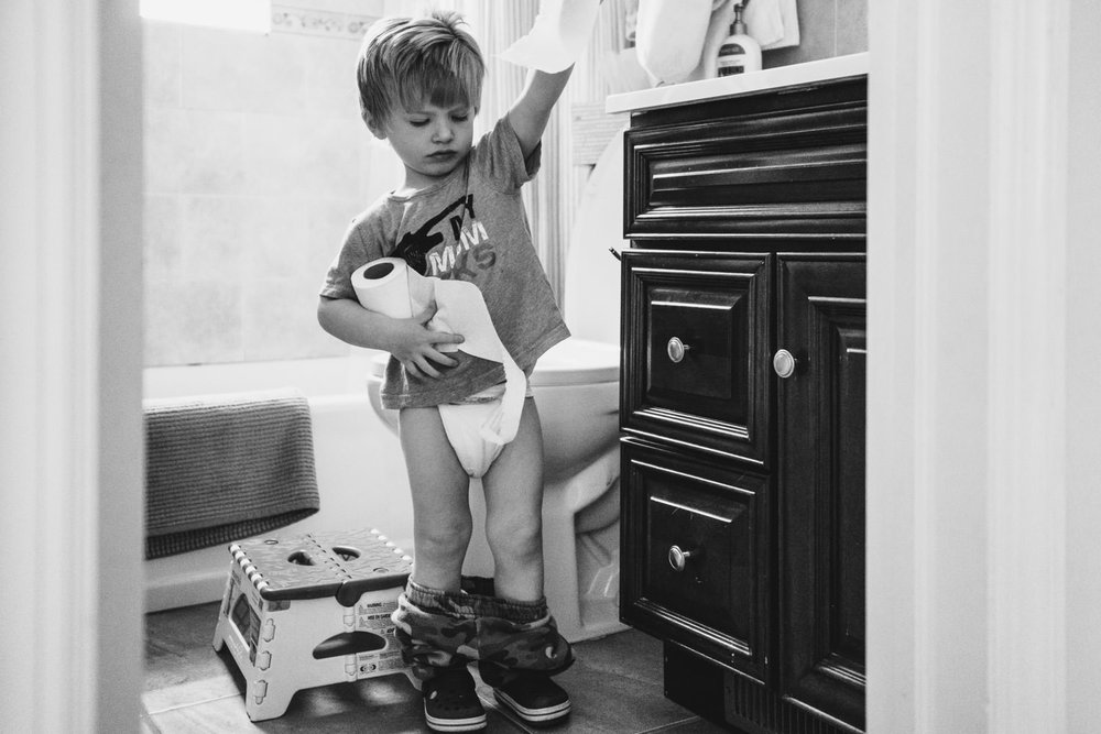 A little boy with his pants down (but diaper on), pulls a piece of toilet paper off the roll.