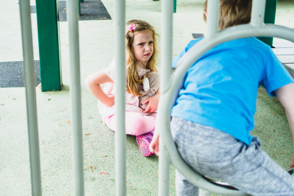 A little girl looks grumpily at her brother on the playground.