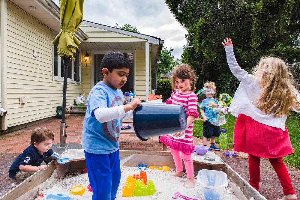 Kids play in the backyard sandbox.