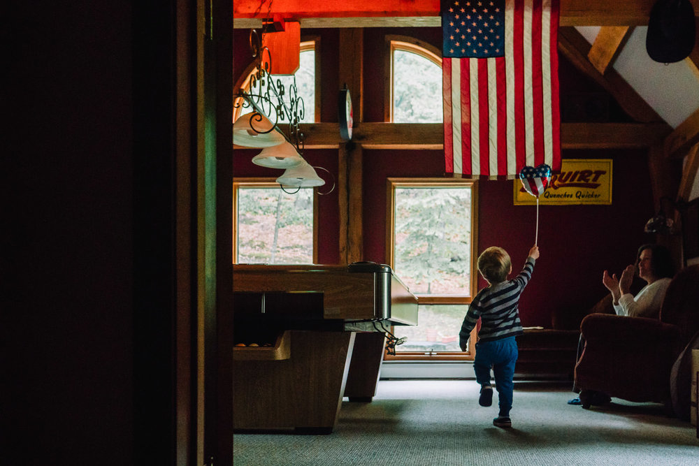 A little boy marches under an American flag with a stars and stripes balloon.