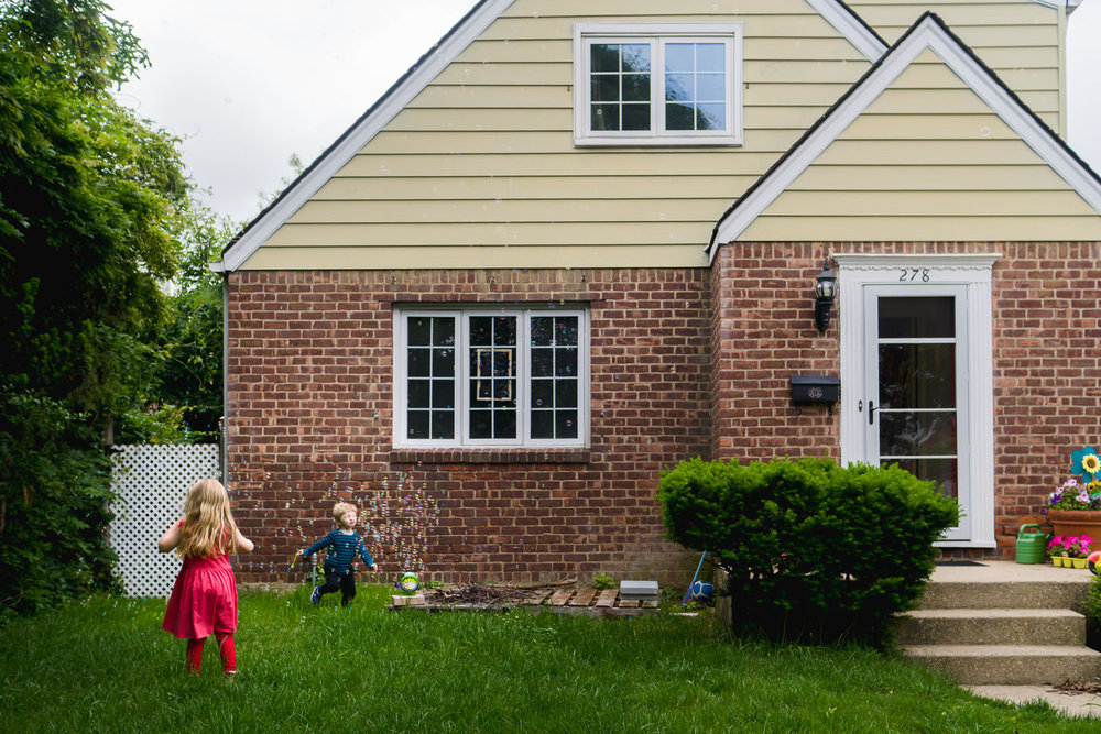 A boy and girl play with bubbles outside their house.
