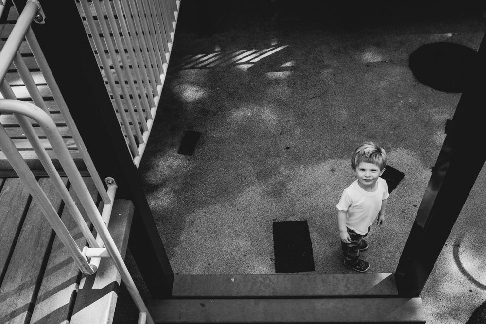 A little boy looks up at the camera while on the playground.