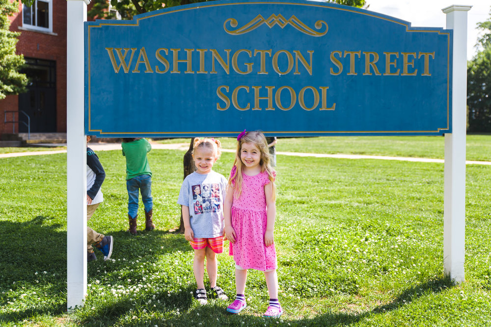 Two little girls stand under the sign to their school.