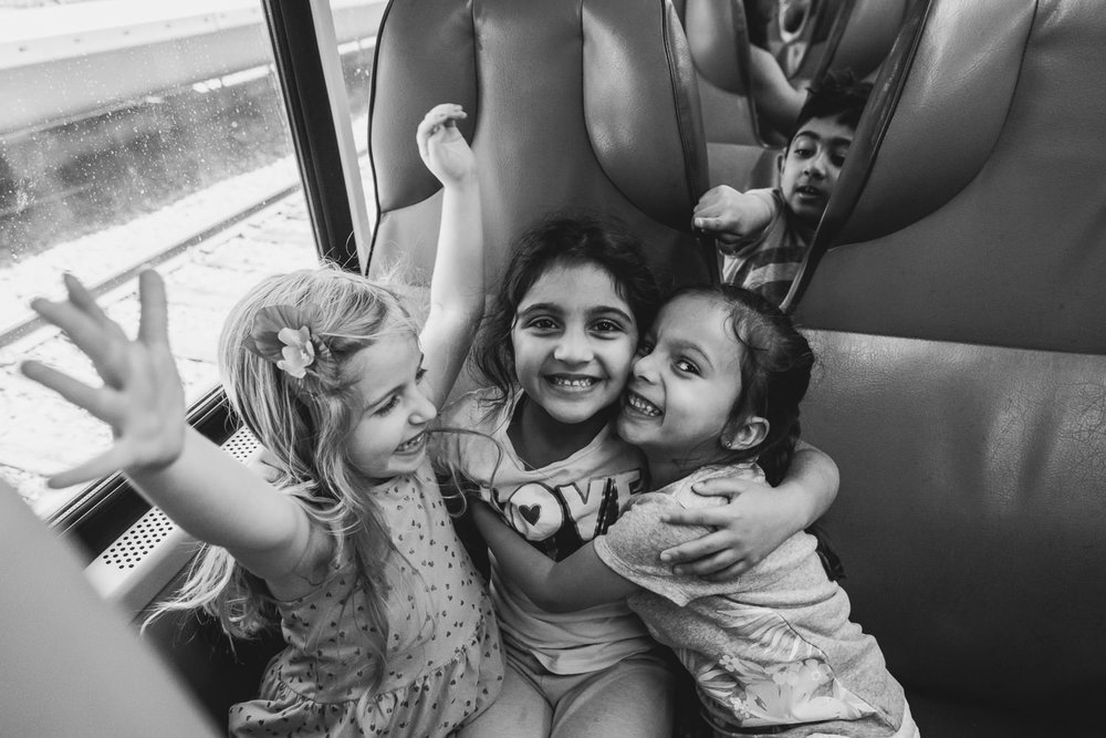 Girls embrace on the Long Island Railroad.
