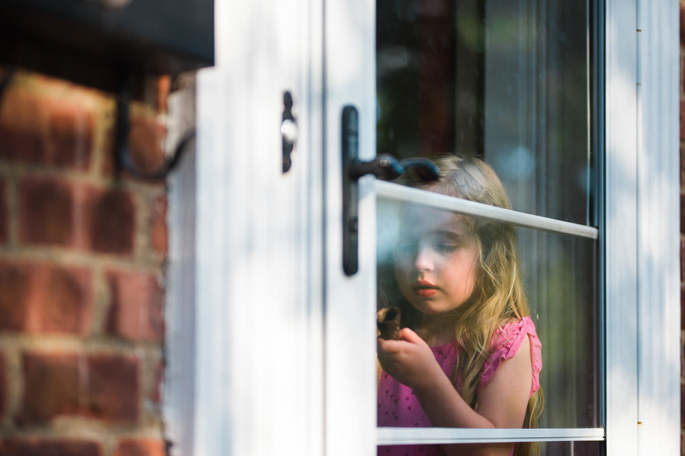 A little girl eats an ice cream cone behind a glass storm door.