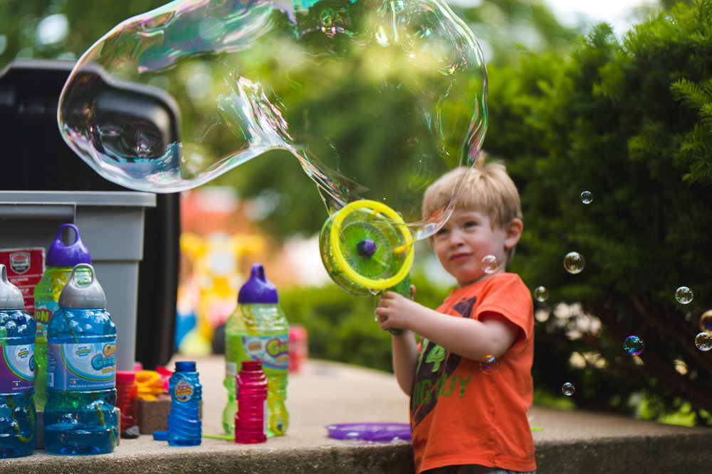 A little boy blows an enormous bubble with a bubble gun.