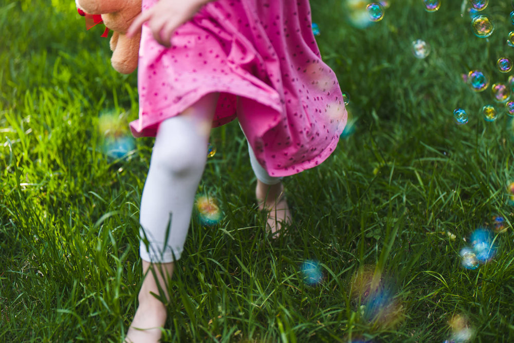 A girl runs through green grass and bubbles.