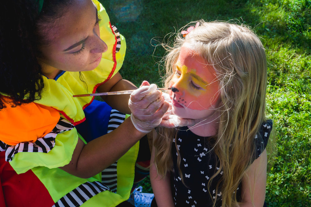 A little girl gets her face painted like a tiger.