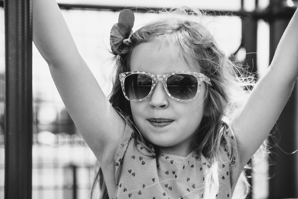 Black and white portrait of a little girl in sunglasses.