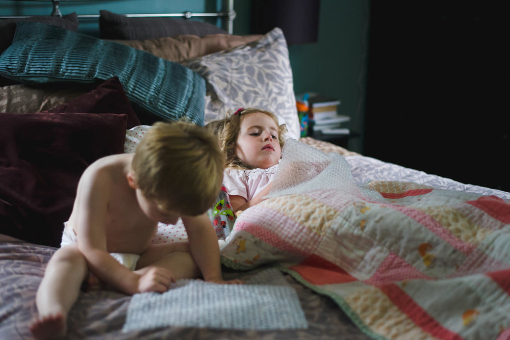 Kids camped out on parents' bed playing with bubble wrap.