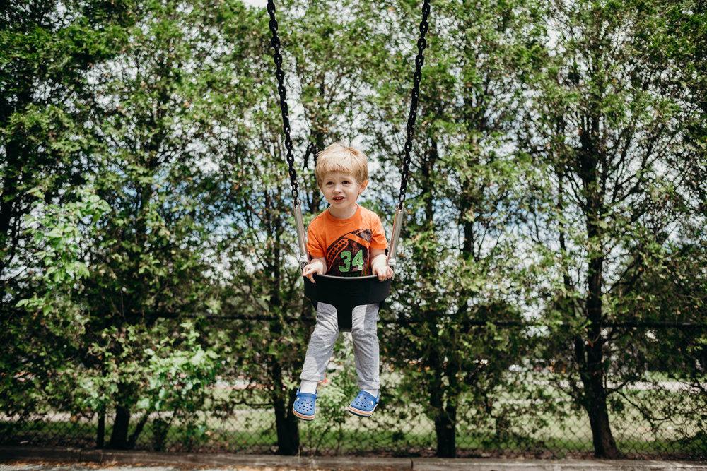 A little boy on a swing.