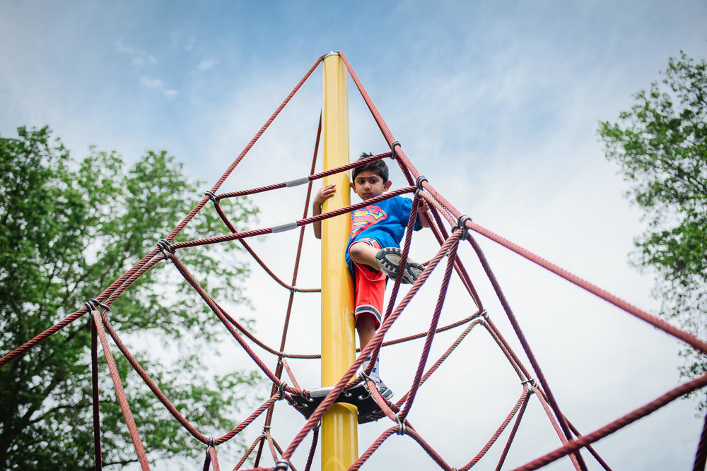 A little boy climbs to the top of a play structure.
