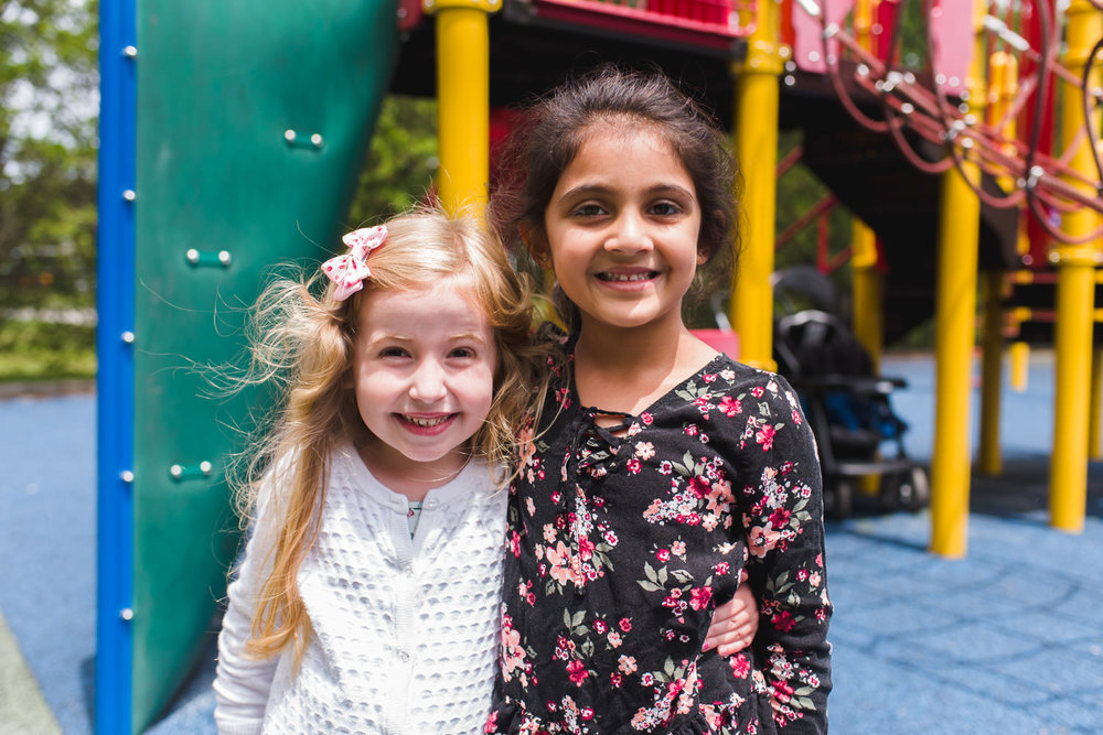 Two preschool girls smile for the camera.