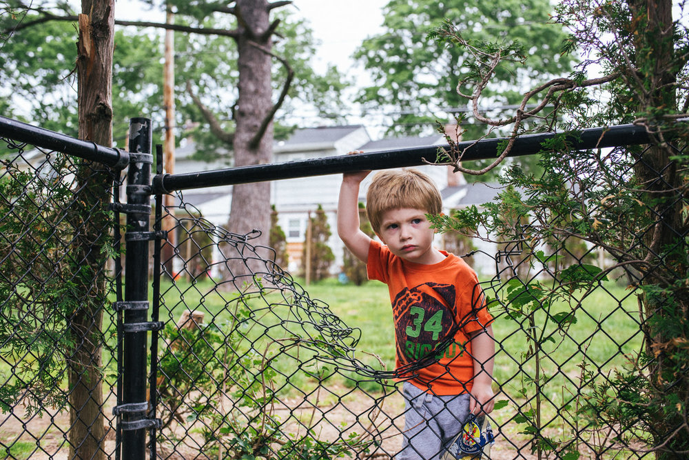 A little boy stands by a hole in a fence, looking angry.