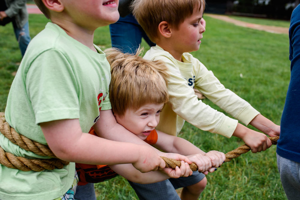 A little boy gets squished between two others in a game of tug of war.