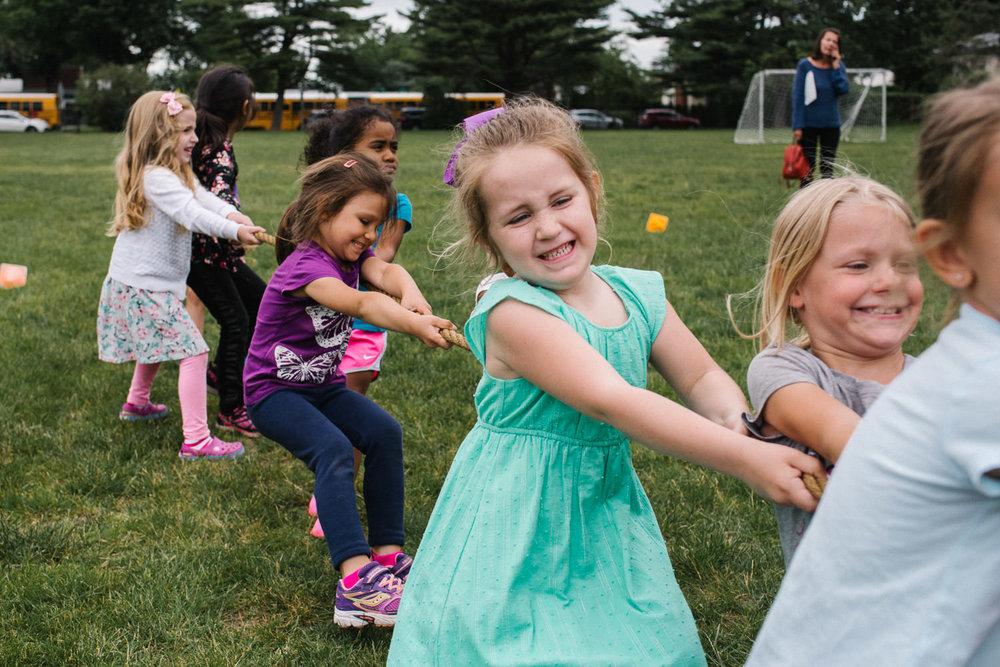 Preschool girls play tug of war.