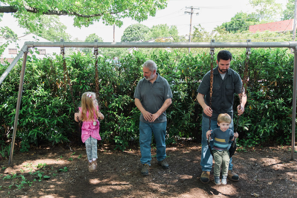 Dad and Grandpa push kids on the swings.