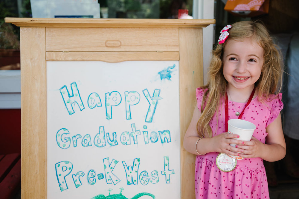 "A little girl stands by a sign that says ""Happy Graduation Pre-K West"""