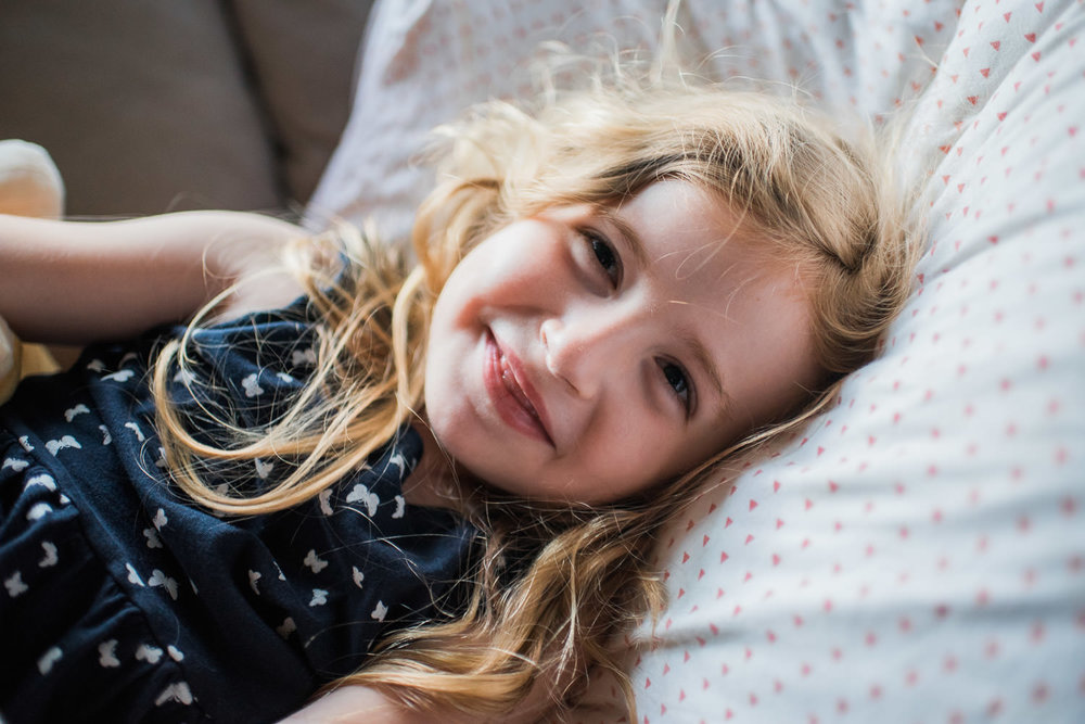 A little girl smiles, lying down on her pillow.