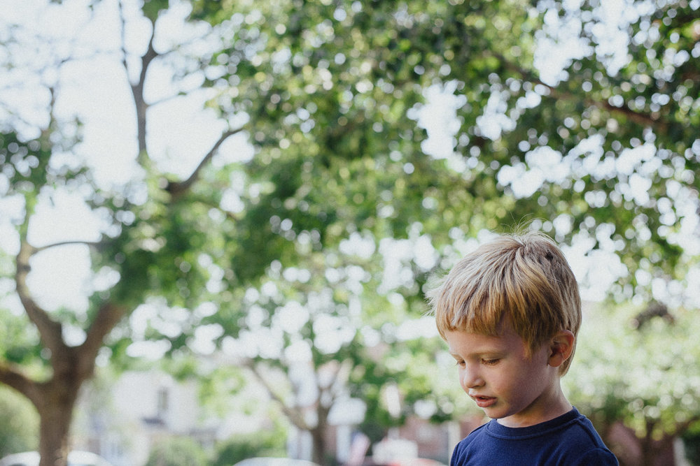 Portrait of a little boy in front of a tree.