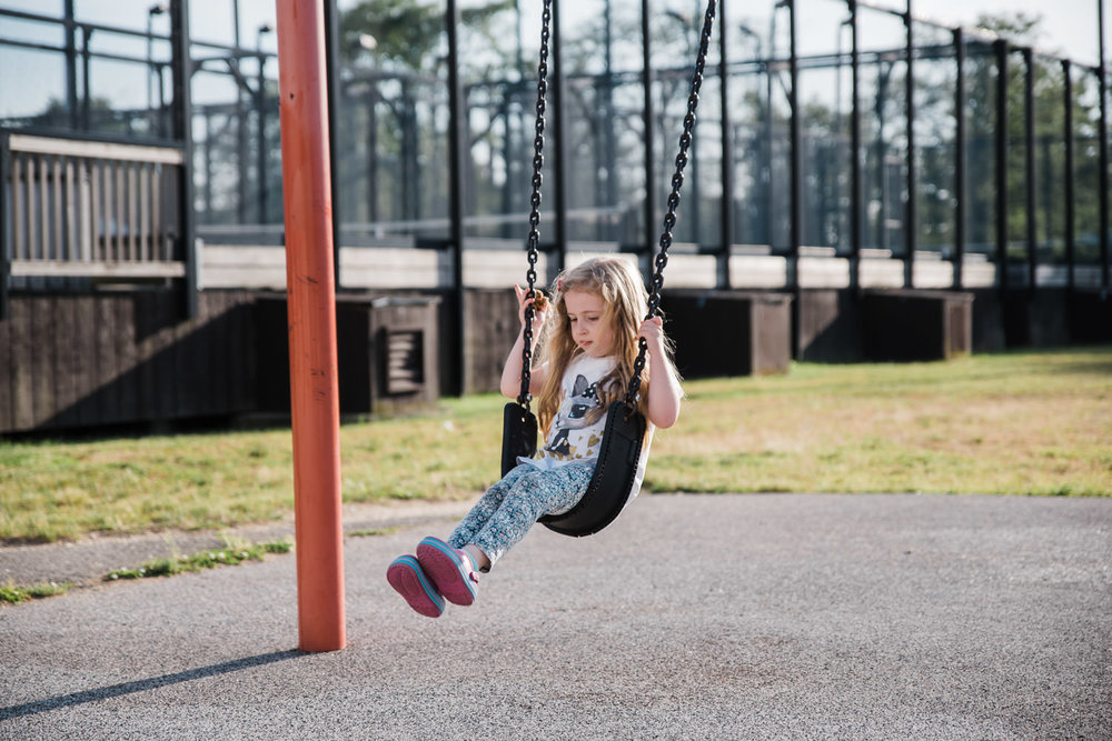 A little girl swings on a swing at the playground.