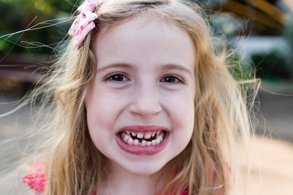A little girl shows off her loose tooth.