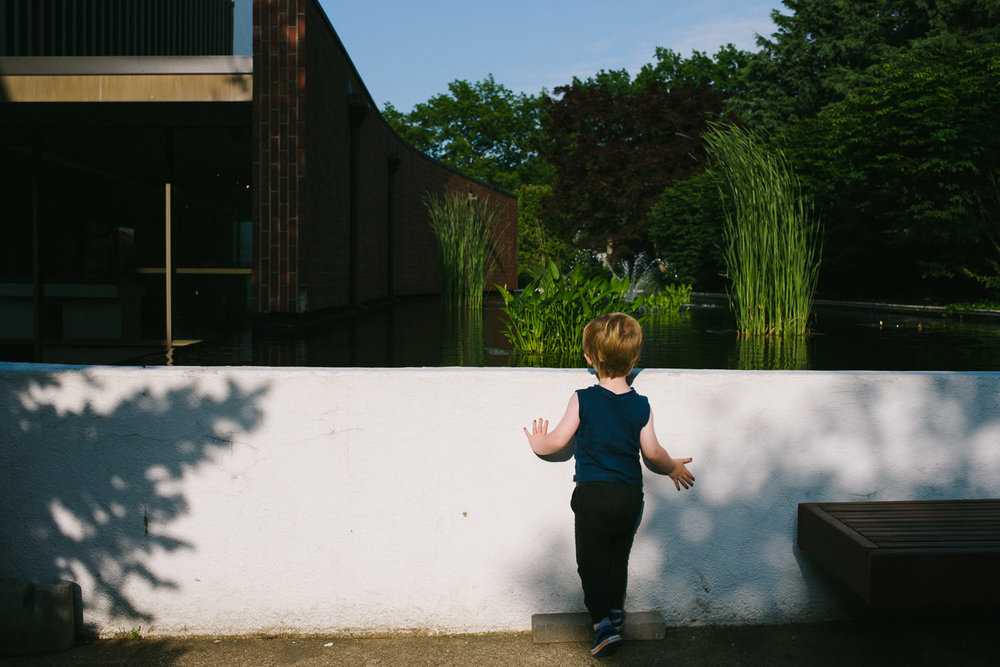 A little boy peers over a white wall.