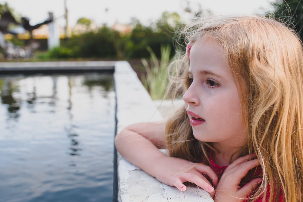 A little girl looks out at a reflecting pool.