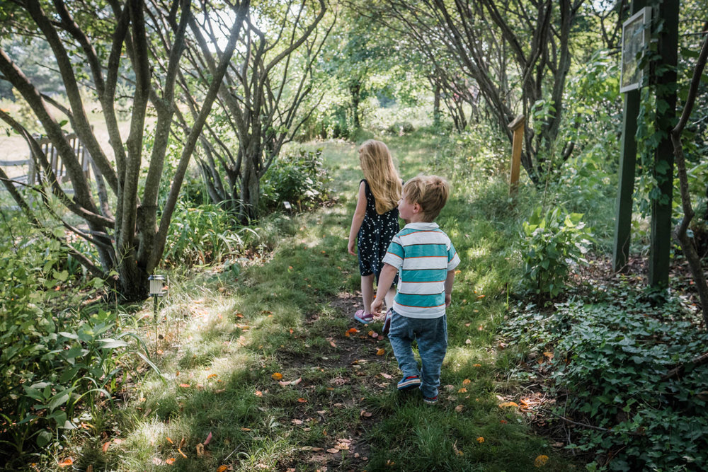 A boy and girl walk on a grassy wooded trail.
