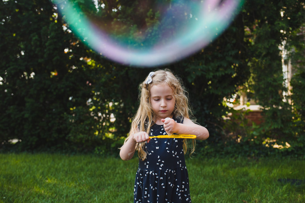 A little girl plays with a bubble wand as a large bubble floats overhead.