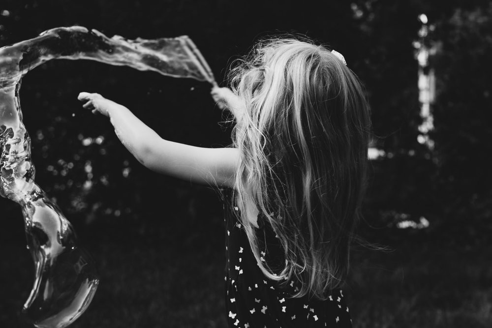 A little girl twirls around with a bubble wand, trailing bubbles.