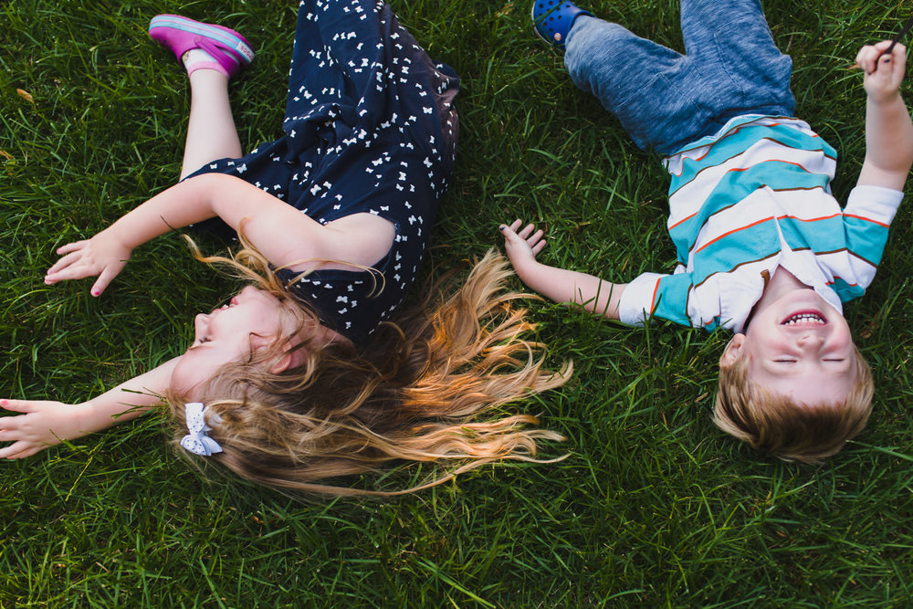 A boy and girl roll around on their front lawn.