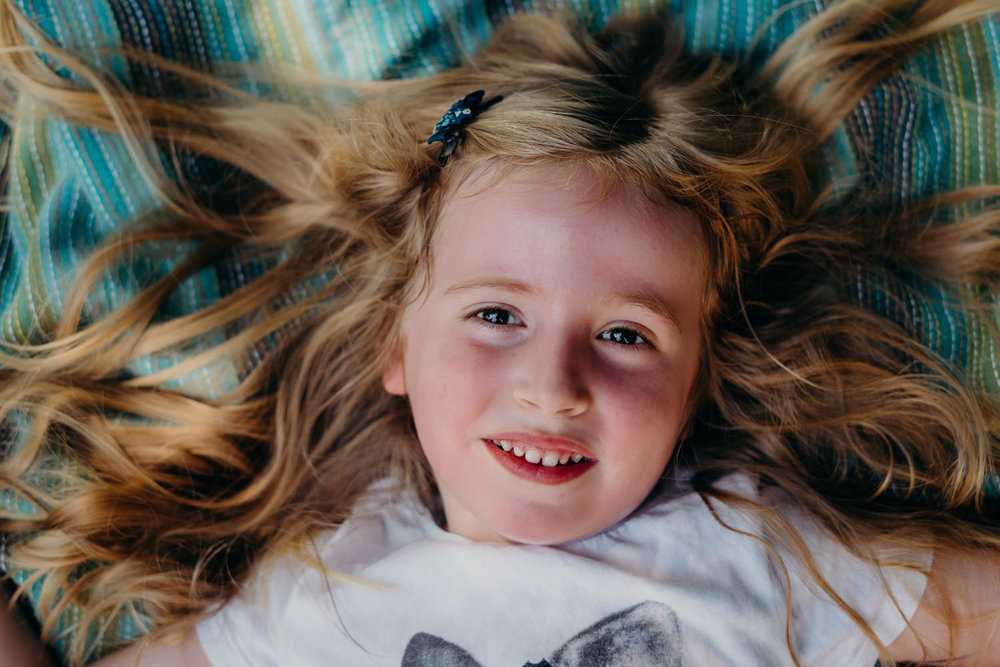 A portrait of a little girl lying on a blanket, her long hair spread out around her.