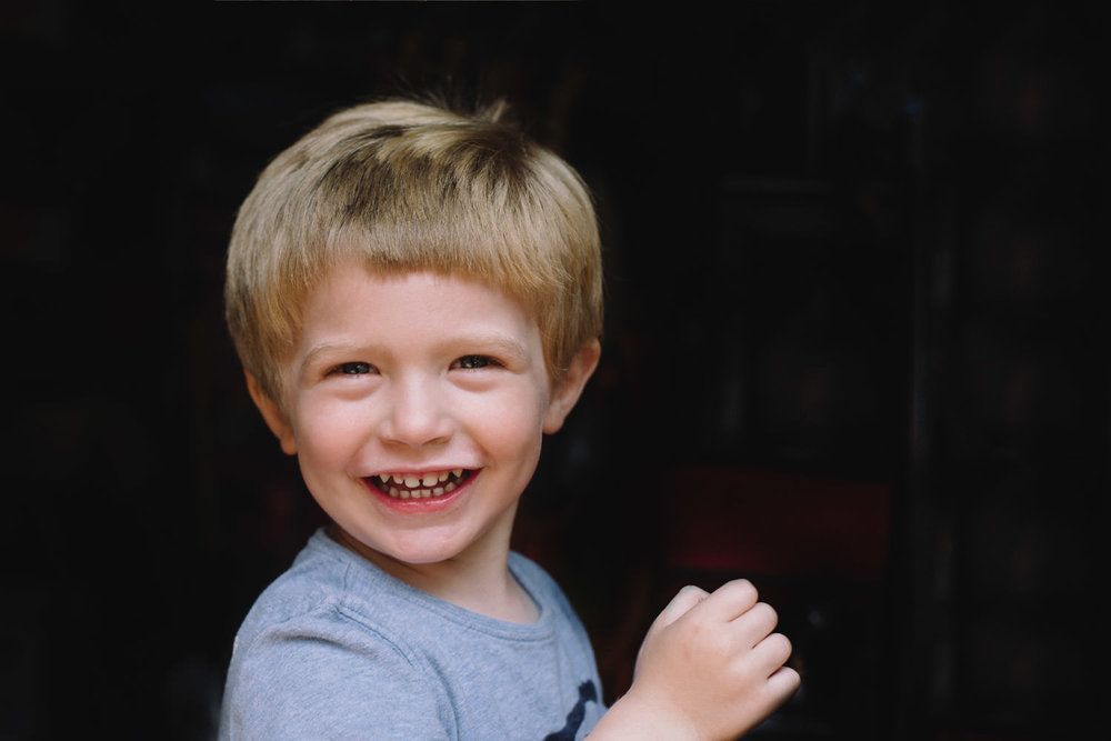 A portrait of a three year old blonde boy smiling.