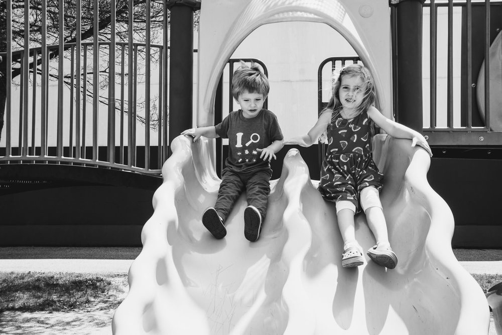 Siblings go down the slide.
