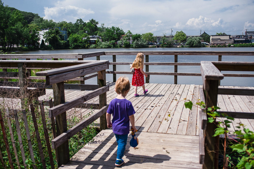 Children walk on the pier at the Roslyn Duck Pond.